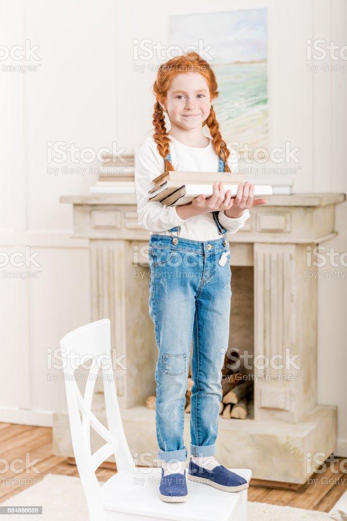 Adorable jeune fille souriante debout sur la chaise et la tenue de livres - Photo