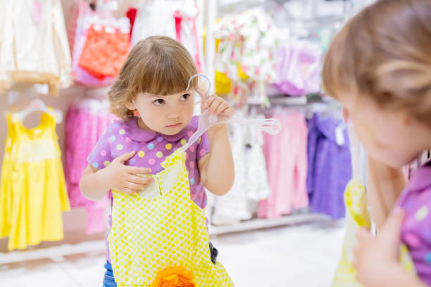 Adorable smiling little girl at the clothes store, try on new yellow summer dress stock photo