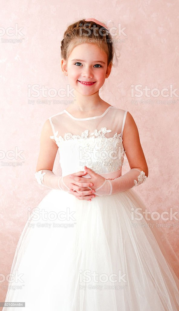 Adorable smiling little girl in white princess dress stock photo