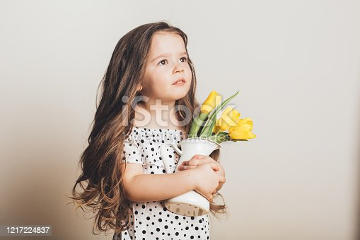 Adorable smiling little girl with yellow tulips. Long hair, International Women's Day, 8 march, Spring Festival, Easter, positive and fun.