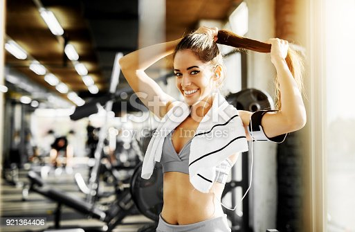 istock Adorable smiling shape fitness girl preparing her hair for exercise in the gym and looking at the camera. 921364406