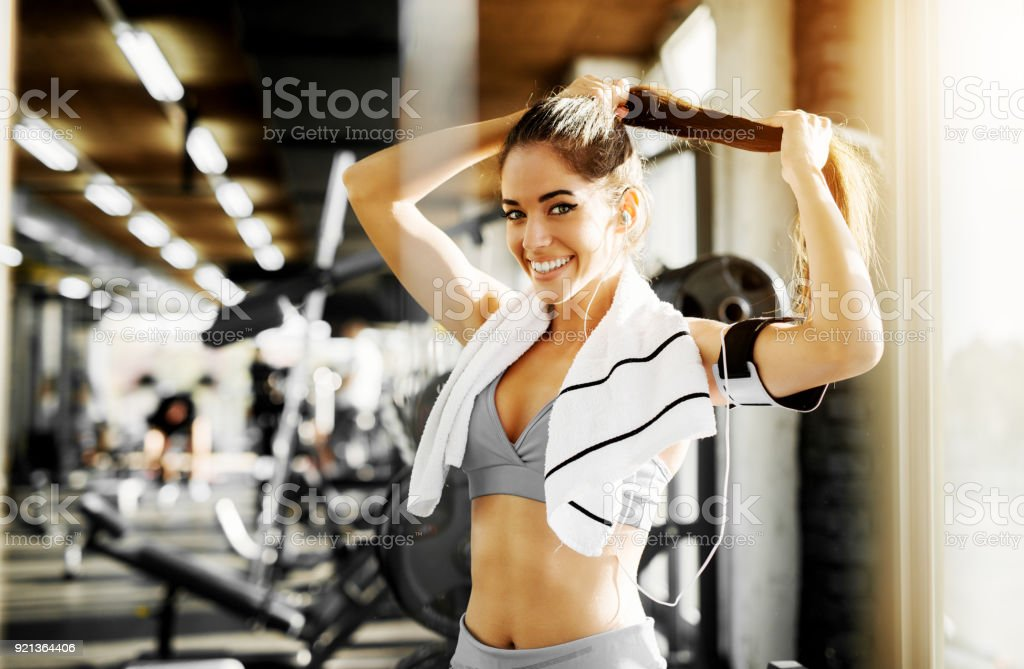 Adorable smiling shape fitness girl preparing her hair for exercise in the gym and looking at the camera. stock photo