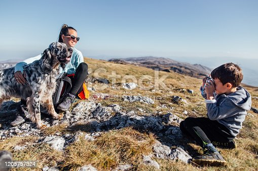 Mother son and their dog English setter, enjoying the view from the top of the mountain while boy taking picture of them and view