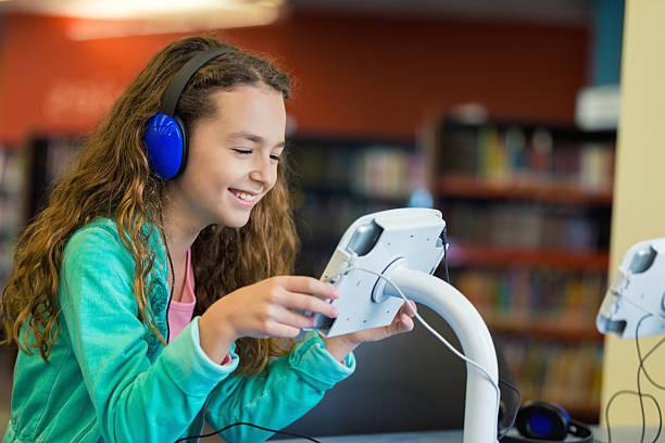 hübsche student mit digitalen tablet in der grundschule-bibliothek - lautbildungsspiele stock-fotos und bilder