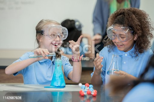 istock Adorable student with Down Syndrome laughs while doing chemistry experiment with classmates 1142687628