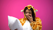 Adorable tired woman in giraffe pajamas yawning, holding pillow, night time