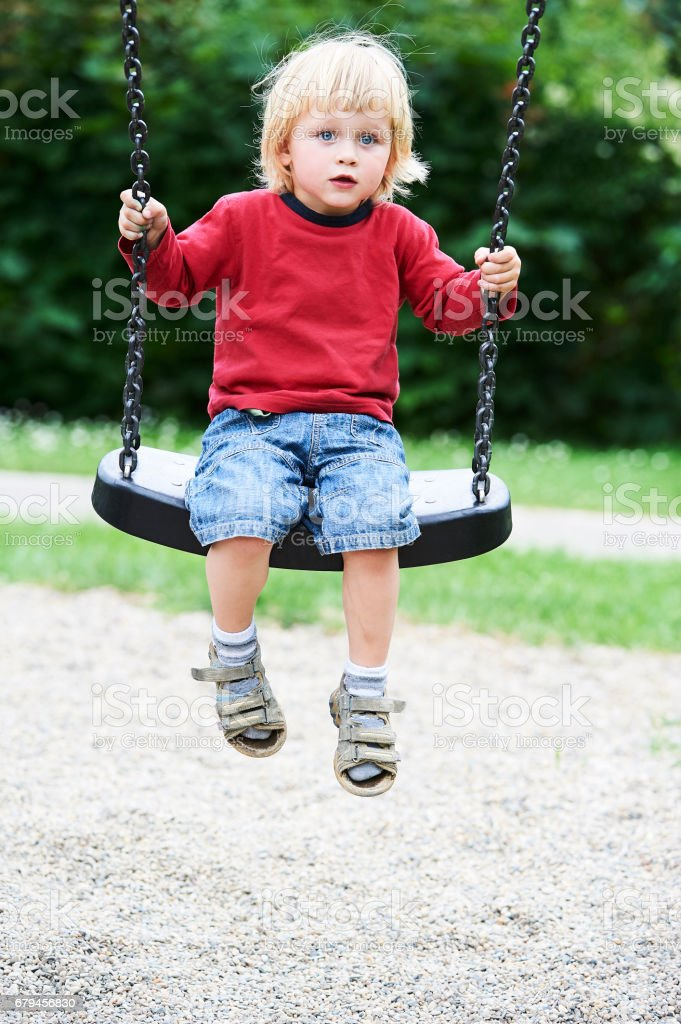 Adorable toddler blond boy having fun chain swing on outdoor playground. royalty-free stock photo