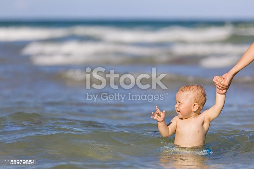 Adorable toddler boy enjoying swimming in the ocean on a sunny day. Mother and child in the sea. Family on vacations. Little child in water, outdoors.