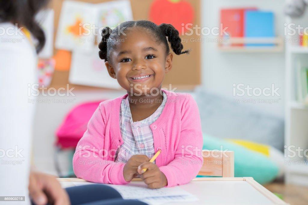 Pretty little girl enjoys drawing in her preschool classroom. She is...