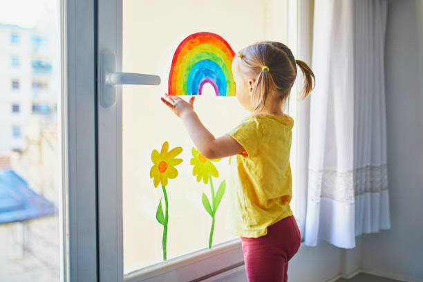 Adorable toddler girl attaching drawing of rainbow to window glass as sign of hope stock photo
