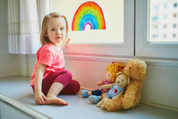 Adorable toddler girl attaching drawing of rainbow to window glass stock photo