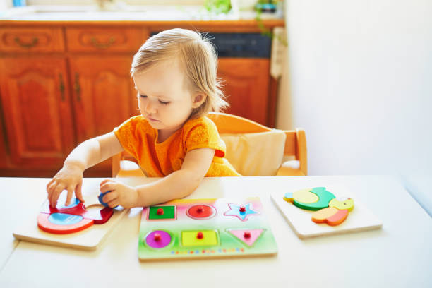 Adorable toddler girl doing wooden puzzle stock photo