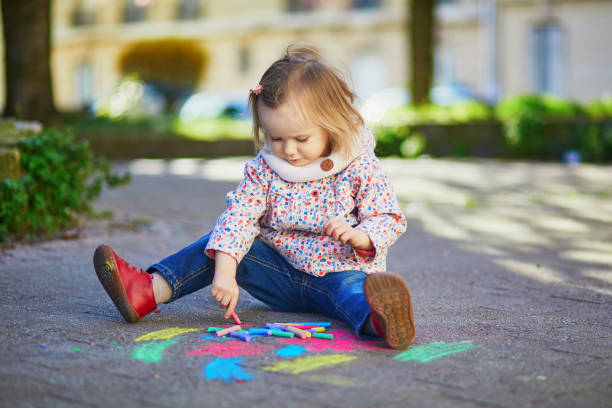 Adorable toddler girl drawing with colorful chalks on asphalt stock photo