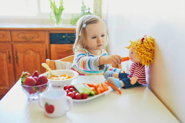 Adorable toddler girl eating fresh fruits and vegetables for lunch stock photo