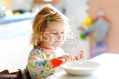 Adorable toddler girl eating healthy porridge from spoon for breakfast. Cute happy baby child in colorful pajamas sitting in kitchen and learning using spoon