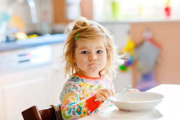 Entzückende Kleinkind Mädchen essen gesunde Porrige aus Löffel zum Frühstück. Süße glücklich Baby Kind in bunten Pyjamas sitzen in der Küche und lernen mit Löffel. – Foto