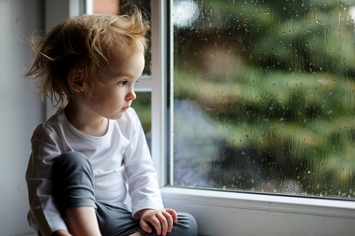 Adorable toddler girl looking though the window