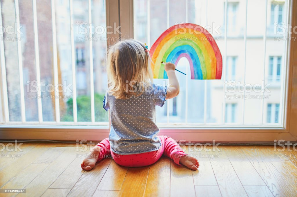 Adorable toddler girl painting rainbow on the window glass Adorable toddler girl painting rainbow on the window glass as sign of hope. Creative games for kids staying at home during lockdown. Self isolation and coronavirus quarantine concept Apartment Stock Photo