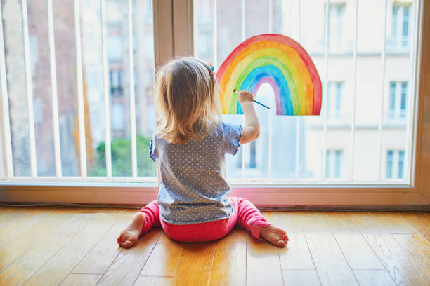 Adorable toddler girl painting rainbow on the window glass stock photo
