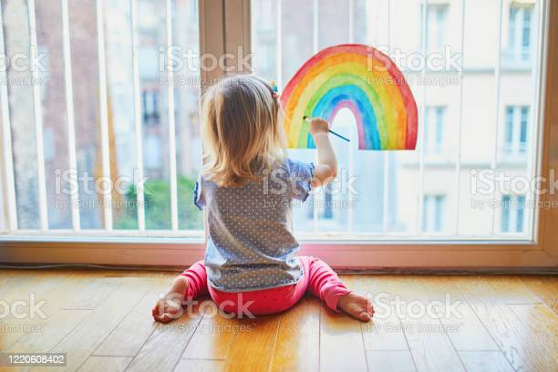 Adorable Toddler Girl Painting Rainbow On The Window Glass Stock Photo - Download Image Now