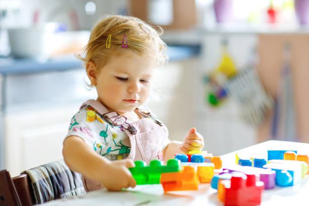 Entzückende Kleinkind Mädchen spielen mit pädagogischen Spielzeug im Kindergarten. Glücklich gesundes Kind Spaß mit bunten verschiedenen Kunststoffblöcke nzuhause. Nettes Baby lernen erstellen und bauen. – Foto