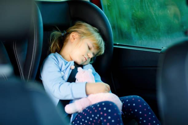 fille adorable d'enfant en bas âge s'asseyant et dormant dans le siège d'auto, retenant le jouet doux peluche et regardant par la fenêtre sur la nature et la circulation. petit gosse voyageant en voiture. sécurité des enfants sur la route. vacan - child car sleep photos et images de collection