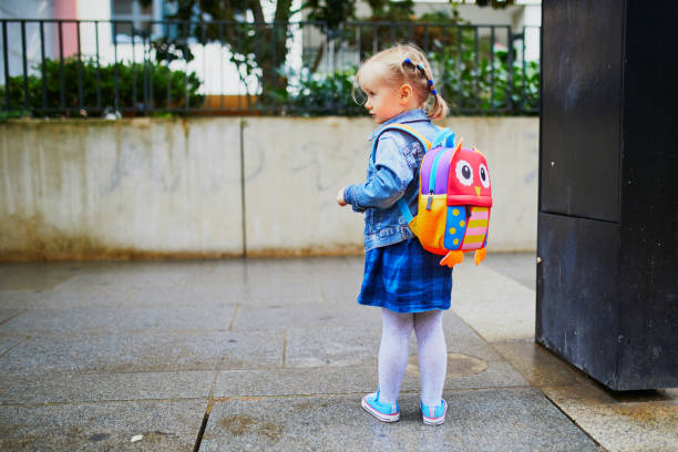 Adorable toddler girl with funny backpack ready to go to daycare, kindergarten or school stock photo
