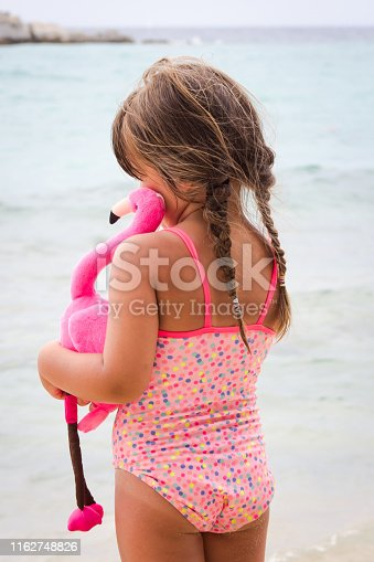 Adorable toddler girl with her favorite flamingo toy on tropical beach. Vacation and travel with kids concept