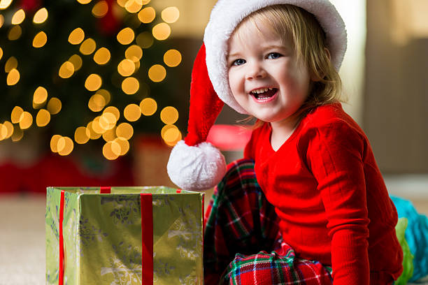 adorable toddler opens gift on christmas morning - little girls giving head stock photos and pictures