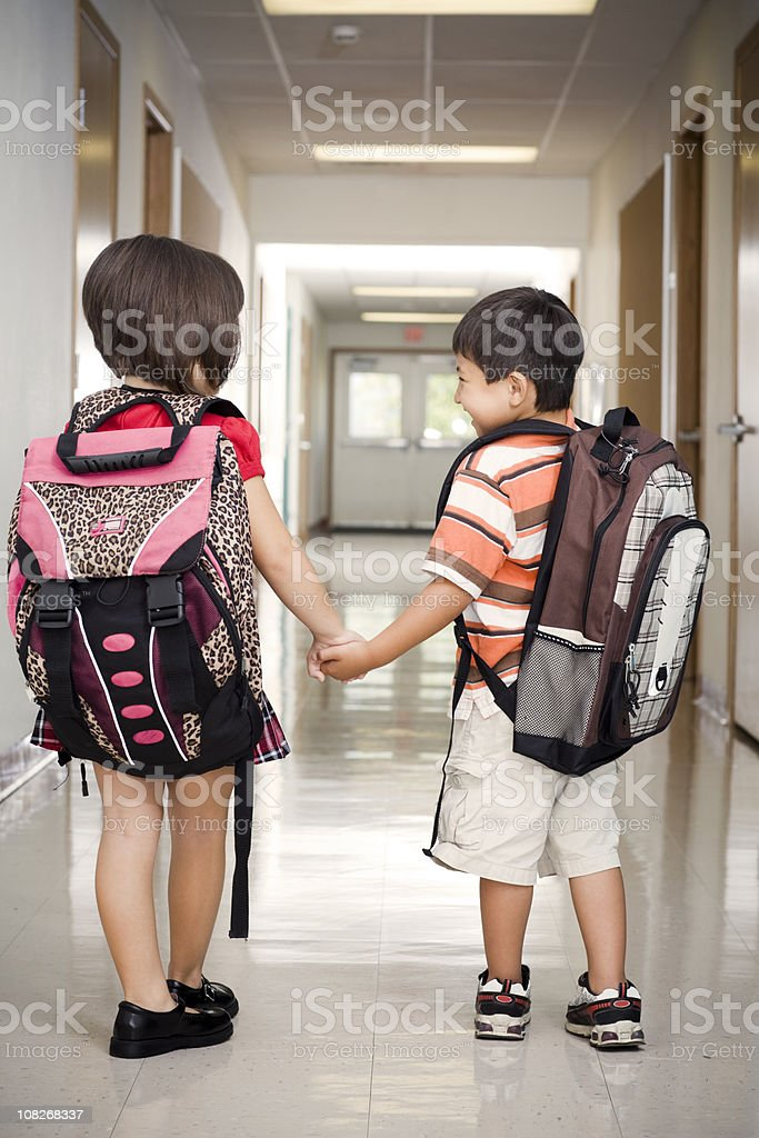 Adorable Two Kids Holding Hands in Elementary School Hallway royalty-free stock photo