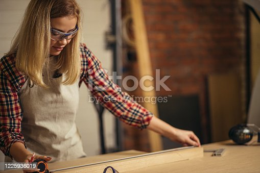 istock adorable woman carpenter use tape-line 1225936019