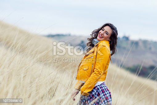 istock Adorable woman with headphones in yellow dress in field 1072595610