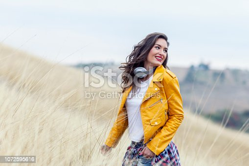 istock Adorable woman with headphones in yellow dress in field 1072595616