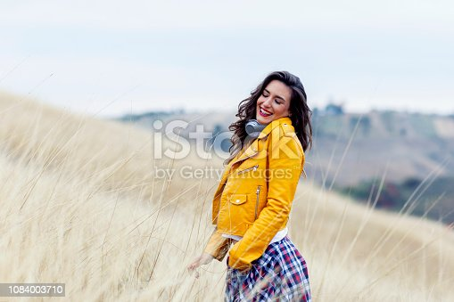 istock Adorable woman with headphones in yellow dress in field 1084003710