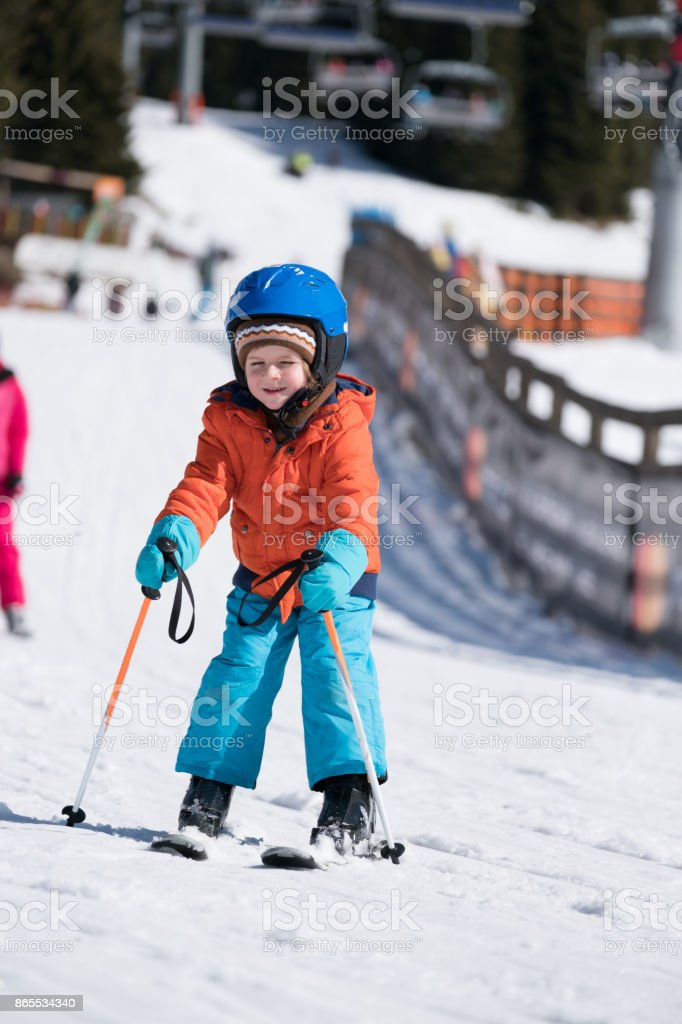 adorable young boy is skiing stock photo