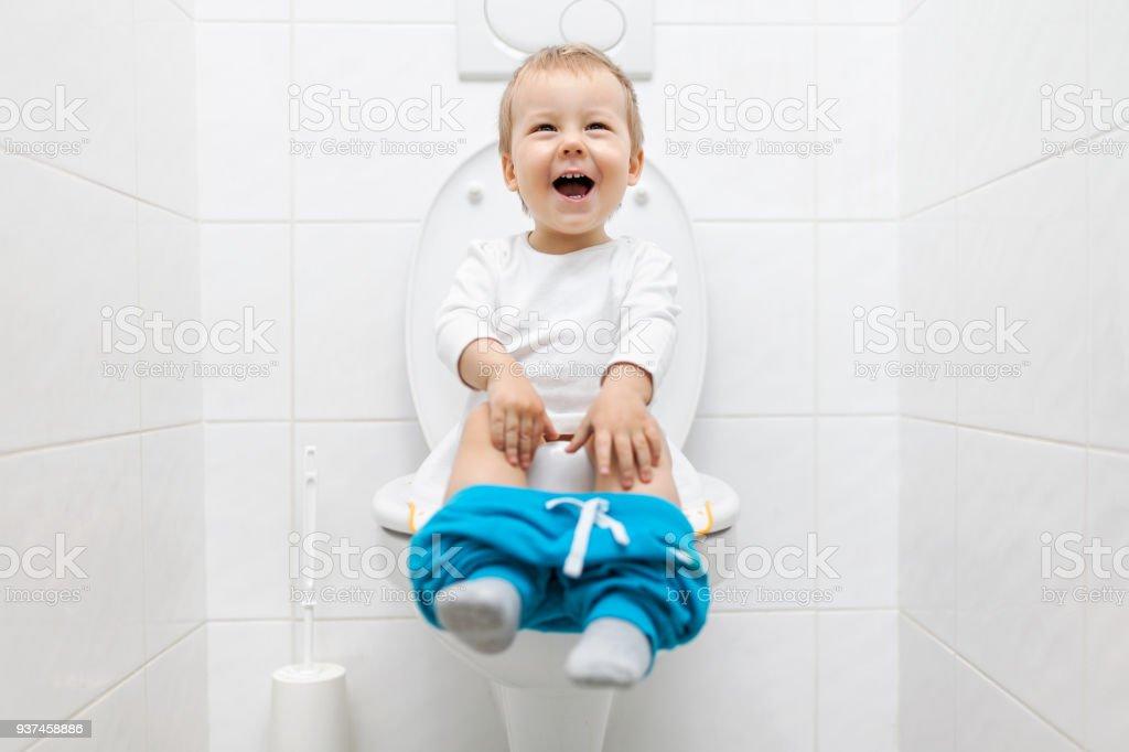 Adorable niño sentado en el inodoro - foto de stock