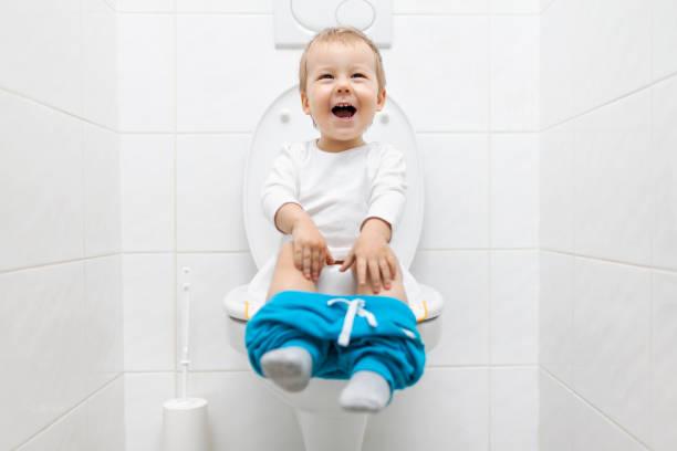 entzückenden jungen kind auf der toilette sitzend - kinder wc stock-fotos und bilder