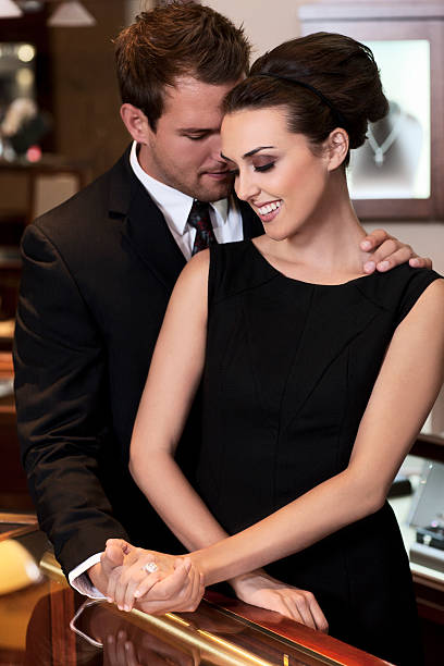 Adorable Young Couple Shopping for Diamond Ring in Jewelry Store stock photo