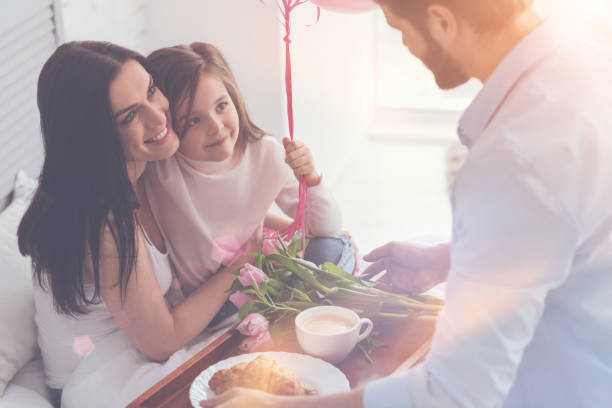 adorable young family making their mom feeling special - mothers day stock photos and pictures