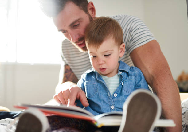 Adorable, young female toddler learning to read book with handsome millennial father on bed stock photo