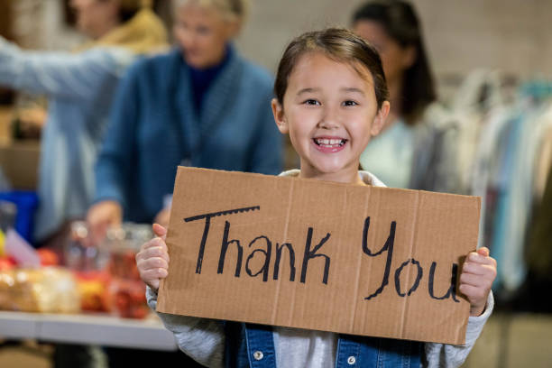 Adorable young food bank volunteer holds 'Thank You' sign Smiling mixed race elementary age girl volunteers with her family in a local food bank. The girl is holding a 'Thank You' sign while smiling at the camera. food drive stock pictures, royalty-free photos & images