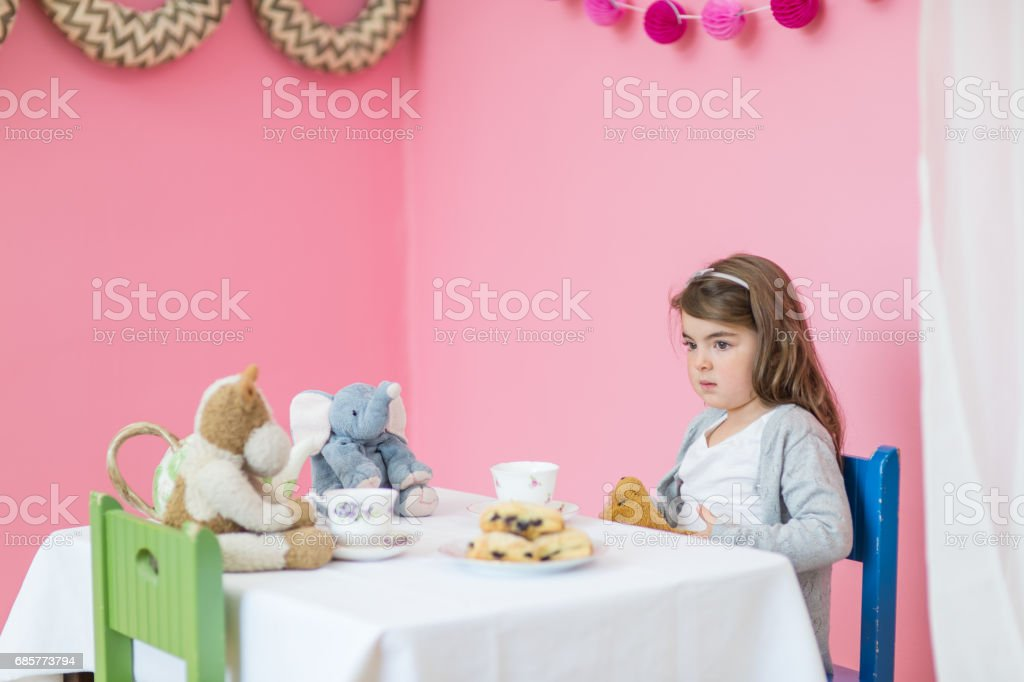 Adorable young girl enjoying an afternoon tea party at the table royalty-free stock photo