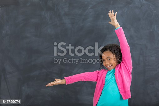 Pretty African American elementary student gestures with her arms in front of a chalkboard in a classroom. She is smiling at the camera.