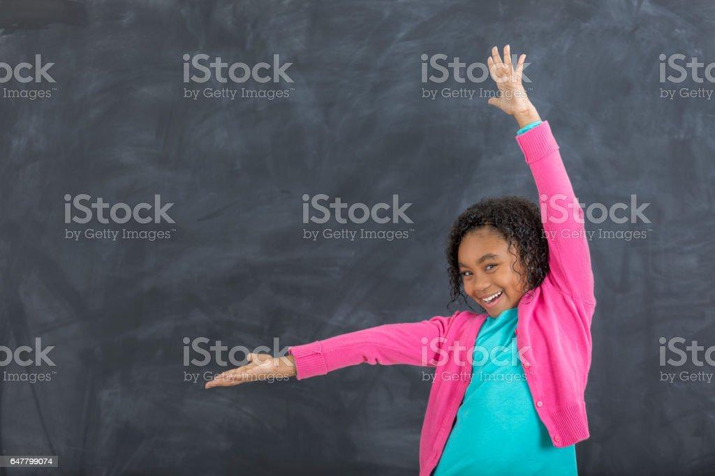 Adorable niña frente a pizarrón en el aula - foto de stock