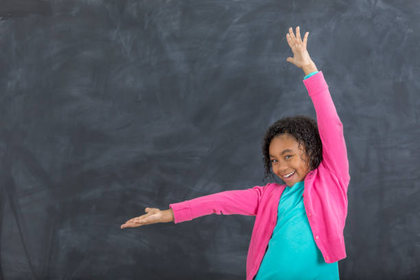 Adorable young girl in front of chalkboard in classroom stock photo