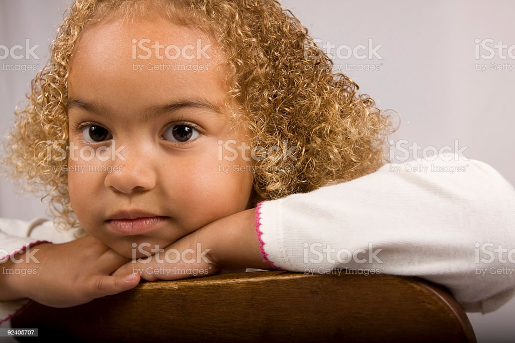 Adorable young girl leaning on chair with big eyes stock photo
