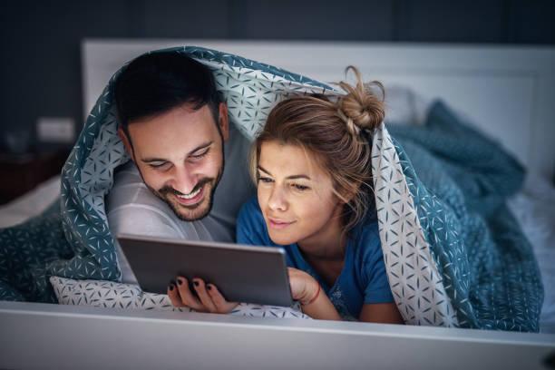 entzückende junge entspannte paar unter decke auf ihre schlechten liegen und lesen von nachrichten auf tablet. eine pause für das wochenende - gute nacht text stock-fotos und bilder