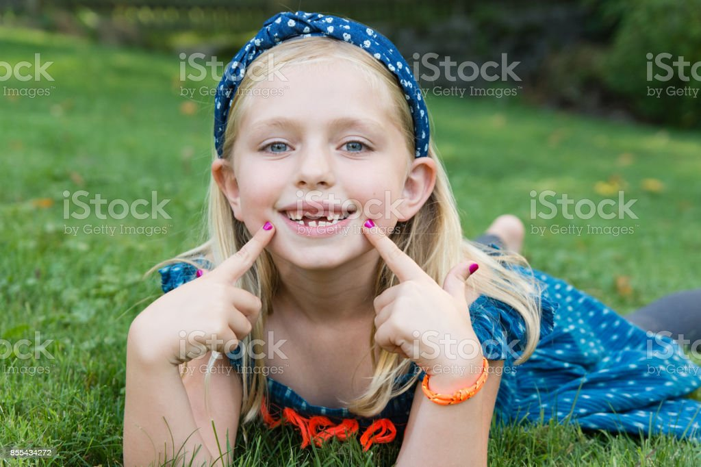 Adorable young school age girl showing gap with missing front two teeth stock photo