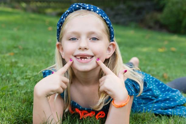 entzückende junge schule mädchen zeigen altersunterschied mit fehlenden zwei vorderzähne - zahnlücke stock-fotos und bilder