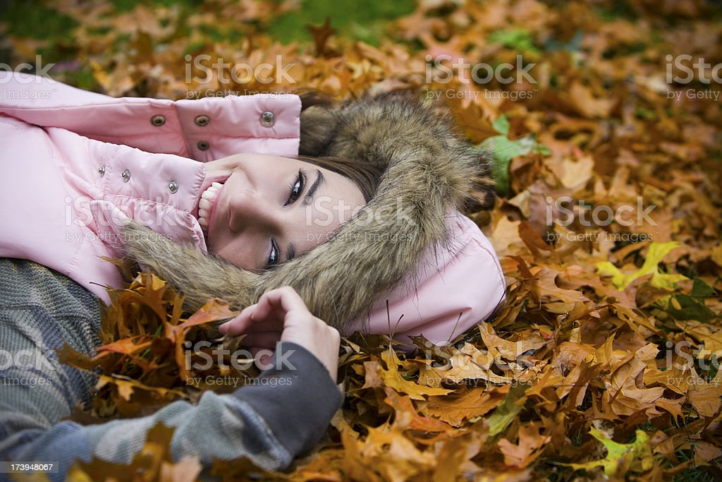Adorable Young Woman Lying in Fall Leaves Outdoors, Copy Space royalty-free stock photo